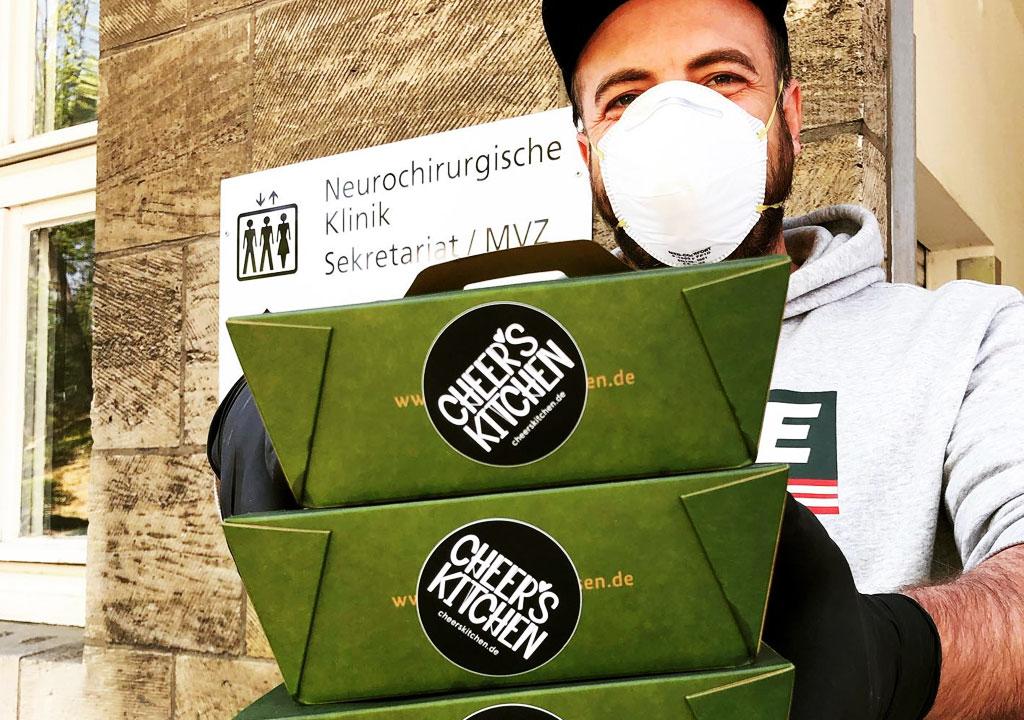 Koch des Monkey Rosé hält drei Essens-Verpackungen einer Cheer's Kitchen Lieferung und trägt einen Mundschutz